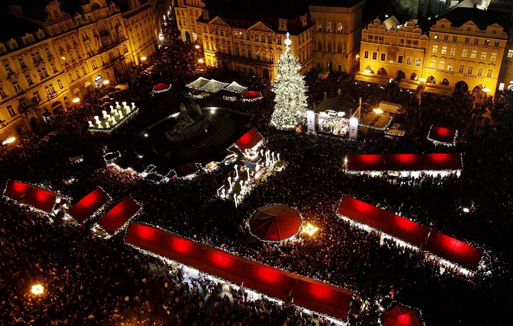 A Christmas tree illuminates the Old Town Square as the traditional Christmas market starts in Prague, Czech Republic. (Petr David Josek/Associated Press))